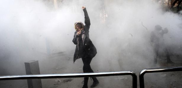 Uma mulher iraniana caminha em meio à fumaça de gás lacrimogêneo na Universidade de Teerã durante protesto impulsionado pela raiva sobre os problemas econômicos, na capital Teerã, em 30 de dezembro de 2017