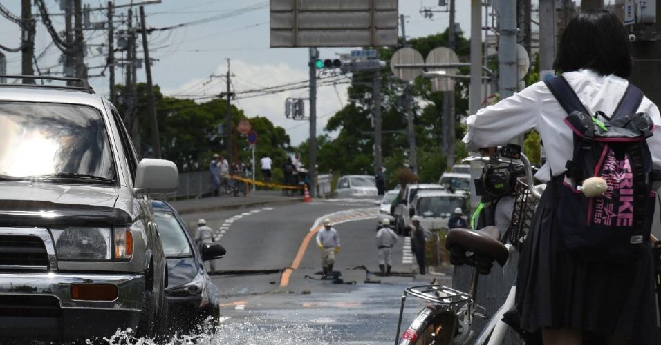 18.jun.2018 - Carros e estudante com bicicleta passam por rua inundada após terremoto em Takatsuki, no norte de Osaka