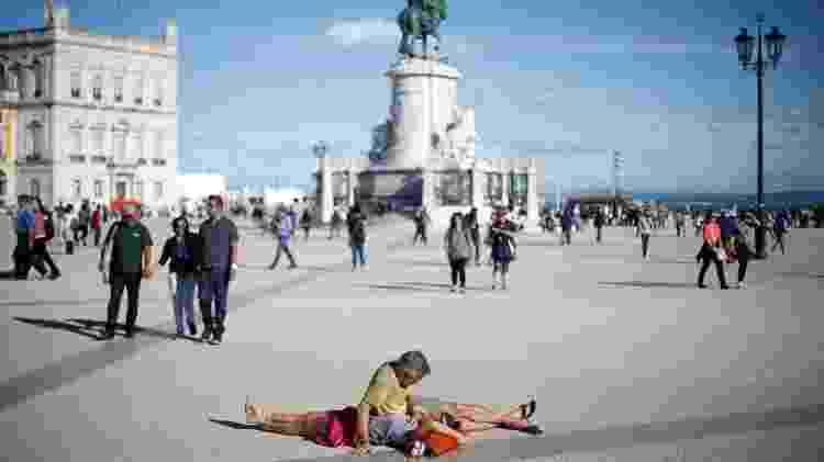 Turistas descansam na praça do Comércio no centro de Lisboa - Rafael Marchante/Reuters