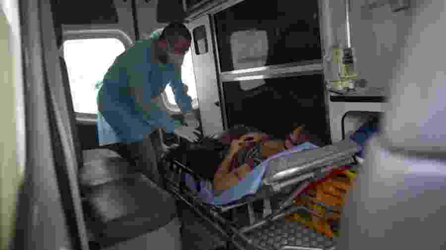 24.mai.2020 - Enfermeiro voluntário Maycon Nogueira prepara paciente com sintomas de covid-19, em ambulância, para transferência até um hospital  - Mauro Pimentel/AFP