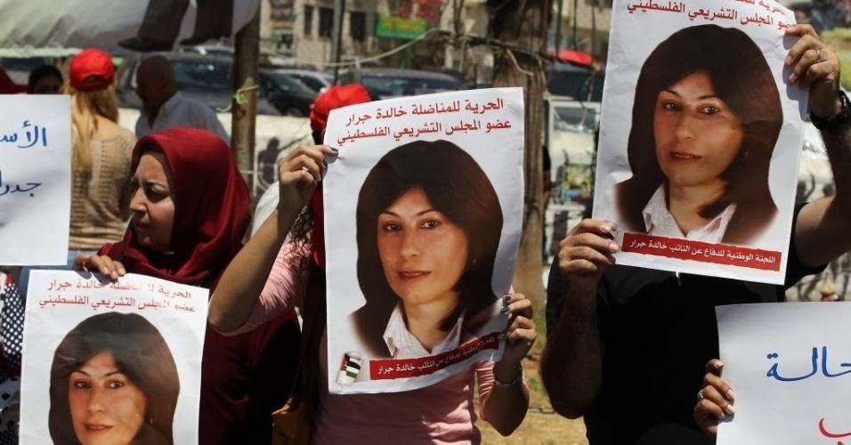11.ago.2015 - Manifestantes palestinos seguram cartazes com a foto de de Khalida Jarrar, membro da Frente Popular Libertação da Palestina, que está detida em uma prisão israelense desde 2 de abril, por representar um suposto