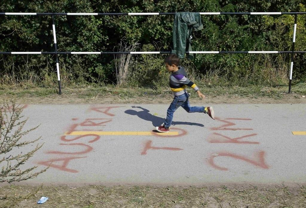 23.set.2015 - Garoto pula sobre indicação da distância para a fronteira da Áustria enquanto imigrantes deixam Hegyeshalom, na Bulgária