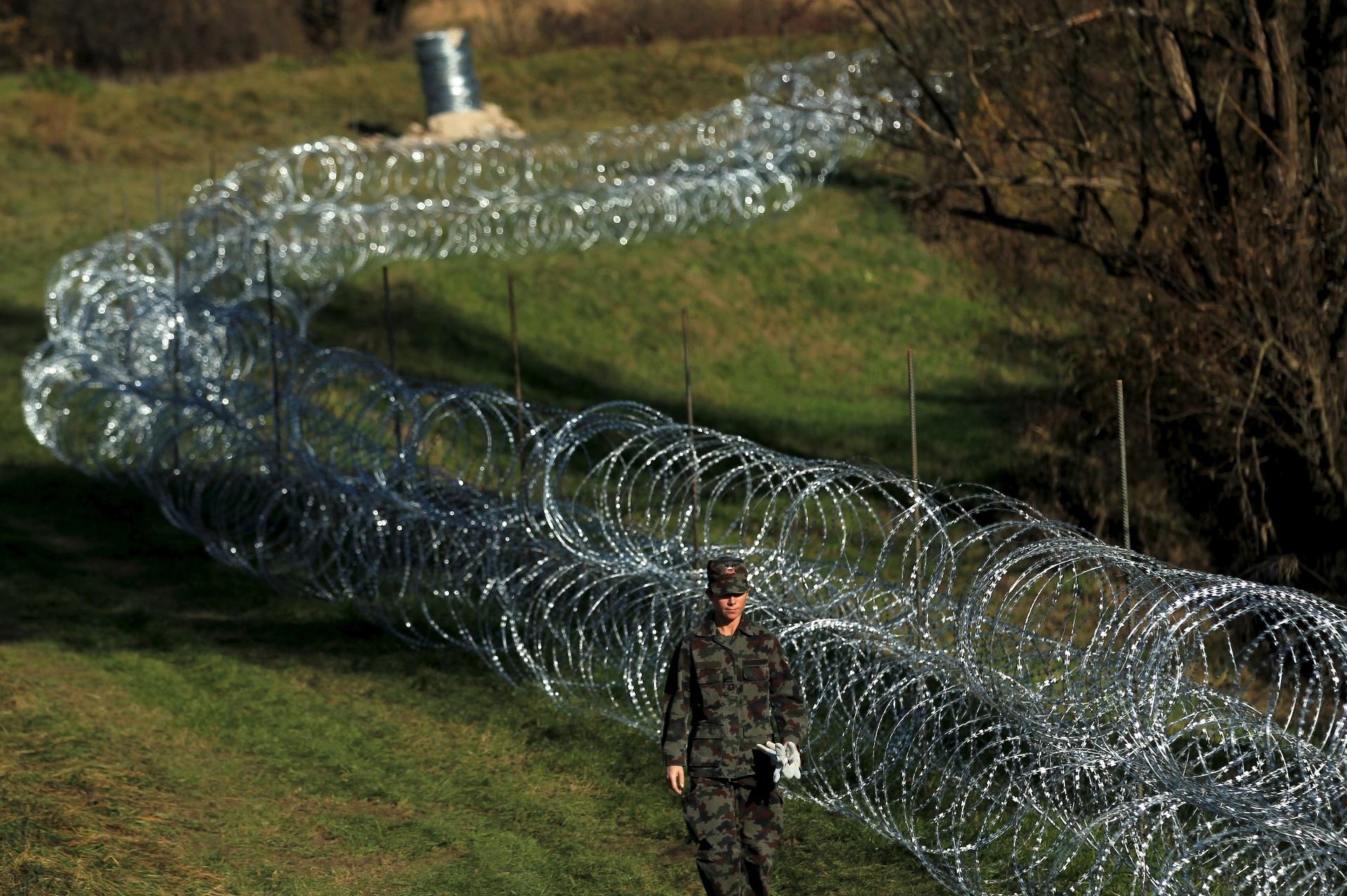 11.nov.2015 - Soldado caminha por cerca de arame armada pelo exército na aldeia de Veliki Obre?, na Eslovênia, próxima da fronteira com a Croácia, um dia depois de o governo esloveno informar que começaria a construção de barreiras para controlar o fluxo de refugiados