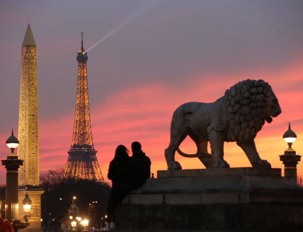 Casal senta perto de estátua de leão para observar o pôr do Sol na Torre Eiffel