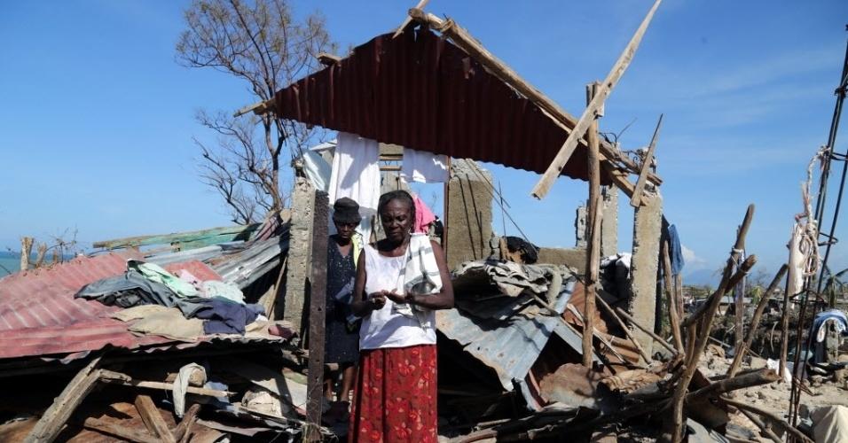 9.out.2016 - Uma pilha de escombros foi tudo o que restou das casas destas duas mulheres no povoado de Jeremie, no Haiti, após a passagem do furacão Matthew. O país decretou luto nacional de três dias a partir deste domingo (9), pelas mortes de centenas de pessoas. O balanço oficial provisório contabiliza, até o momento, 336 mortos, mas este número ainda deve aumentar