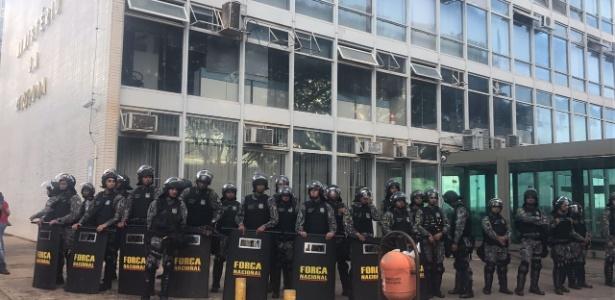 Oficiais da Força Nacional cercam o Ministério da Fazenda após o prédio ser atingido por manifestantes durante protesto em Brasília