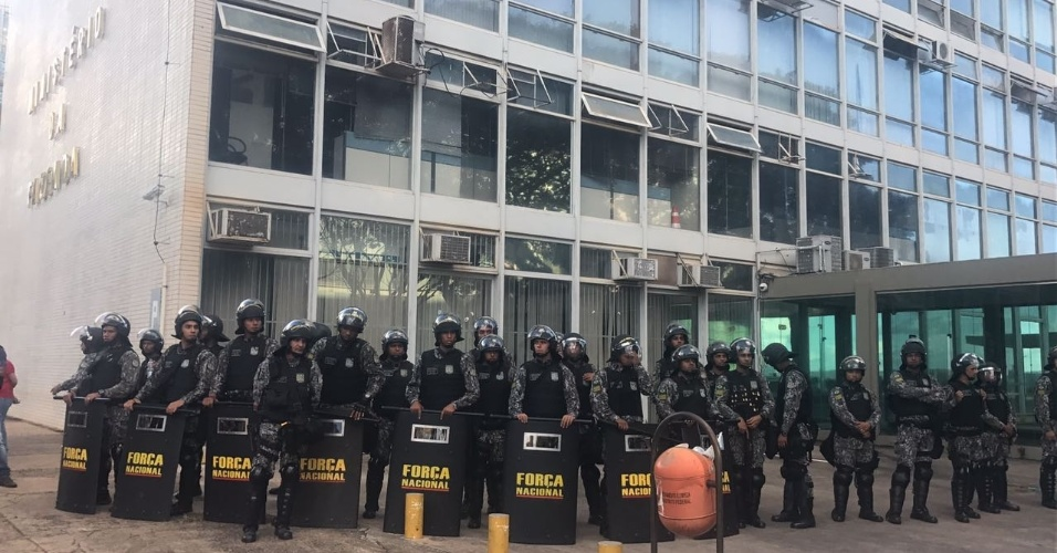 24.mai.2017 - Oficiais da Força Nacional cercam o Ministério da Fazenda após o prédio ser atingido por manifestantes durante protesto em Brasília