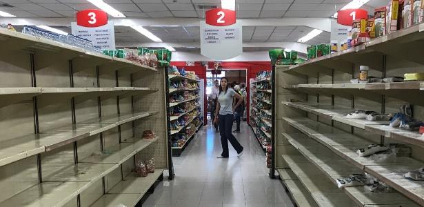 Mulher passa por prateleiras vazias em supermercado de Caracas