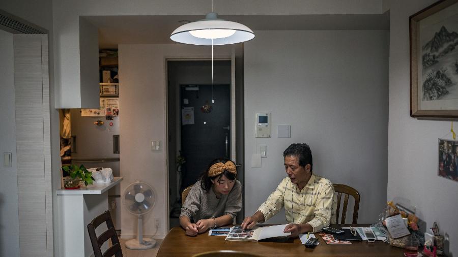 Jiro Oshima e sua neta Misa An olham velhos álbuns de fotos de suas viagens à Coreia do Norte para visitar a família - Andrea DiCenzo/The New York Times