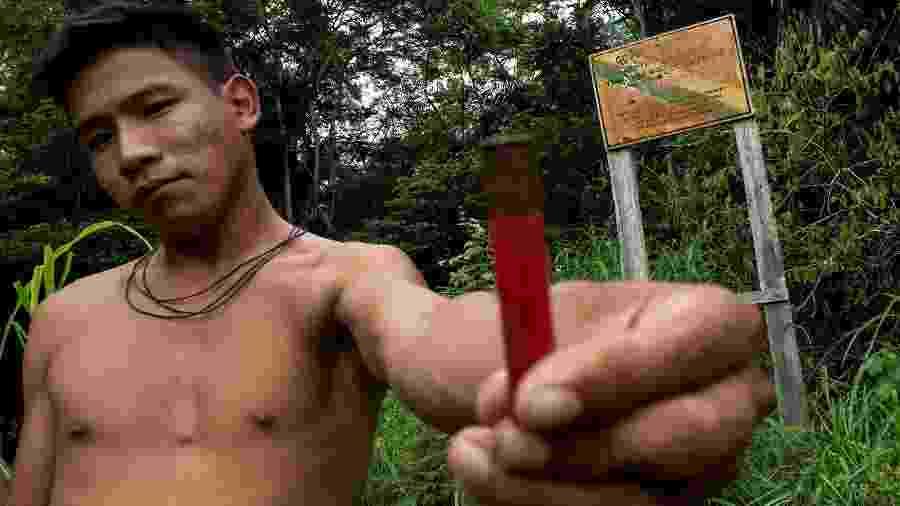 Boatuto, índio do povo Uru-eu-wau-wau, mostra cápsula de munição usada contra placa da Funai que indica os limites da reserva - 31.jan.2019 -  Reuters/Ueslei Marcelino