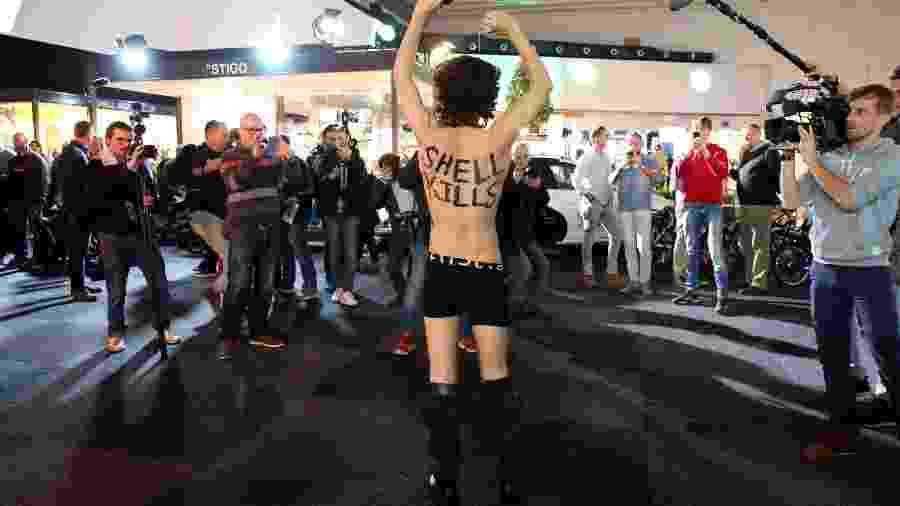 """Ativista do Extinction Rebellion mostra as palavras """"Shell mata"""" pintadas em seu corpo no Salão do Automóvel de Bruxelas - François Walschaerts/AFP"""