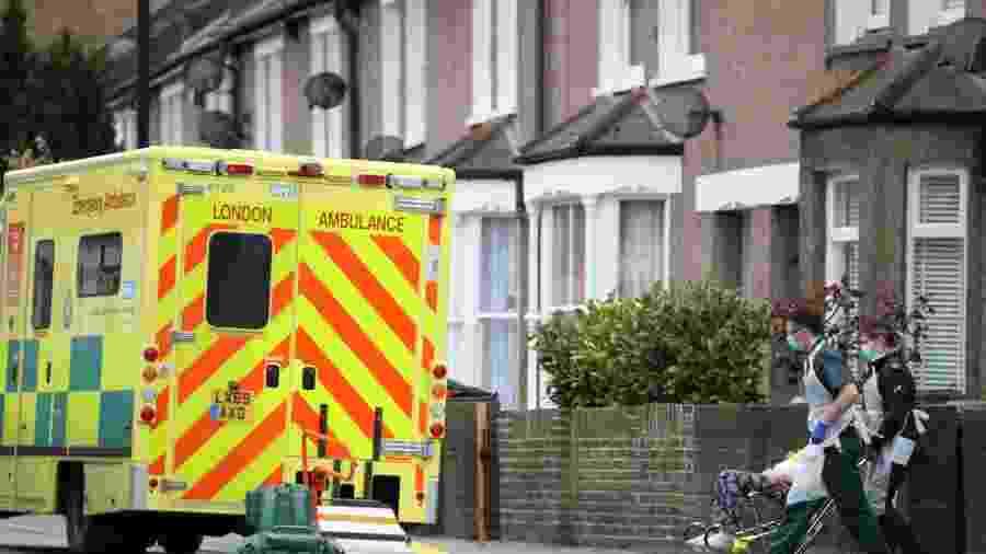 Paramédicos usando máscaras contra coronavírus levam paciente para ambulância em Londres - Hannah McKay/Reuters