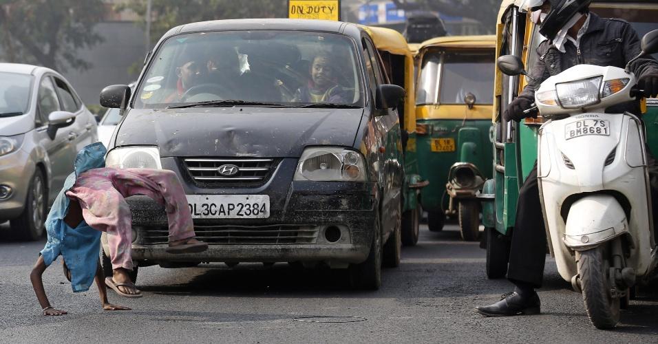 2.jan.2016 - Menino faz acrobacias em frente a automóveis no segundo dia de implementação de um plano de redução de poluição, em Nova Déli (Índia). Autoridades lançaram o plano para limitar o número de carros nas vias e, assim, enfrentar os níveis alarmantes de poluição da cidade, implantando um esquema de rodízio entre os veículos. Com uma população estimada em 17 milhões de pessoas, a capital indiana é a cidade do mundo que mais polui, segundo relatório de 2014 da ONU