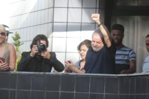 4.mar.2016 - Lula acena da sacada do seu apartamento, após ser conduzido coercitivamente para depor