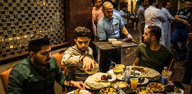 Garçom serve fregueses no restaurante Haju Hussein, em Bagdá, famoso por seu kebab