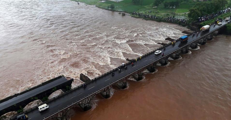 """3.ago.2016 - Indianos observam ponte parcialmente destruída por conta de inundações que atingem o Estado de Maharashtra, no oeste do país. Pelo menos 22 pessoas que viajavam em dois ônibus estão desaparecidas após a queda da ponte, construída antes da independência da Índia, em 1947, perto da cidade de Mahad. Segundo Deepak Pathak, porta-voz da polícia regional, """"outros veículos"""" cruzavam a ponte sobre o Rio Savitri quando houve a queda, por isso o número de vítimas pode ser maior"""