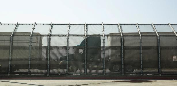 Caminhões entram nos EUA, próximo à fronteira em San Diego, vindos de Tijuana, no México