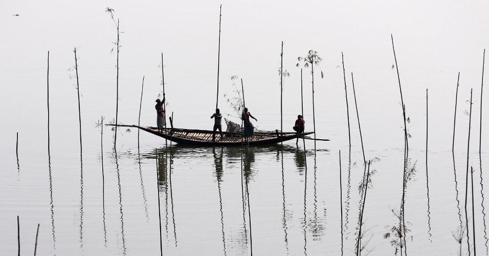 28.nov.2016 - Pescadores colocam bambu, onde mais tarde colocarão galhos de árvores e iscas, para pegar peixes em um rio em Dhaka (Bangladesh)