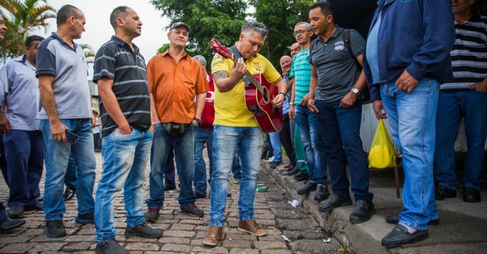15.mar.2017 - Em paralisação, motoristas de ônibus tocam violão na porta de uma garagem na Cidade Tiradentes, zona leste da capital paulista