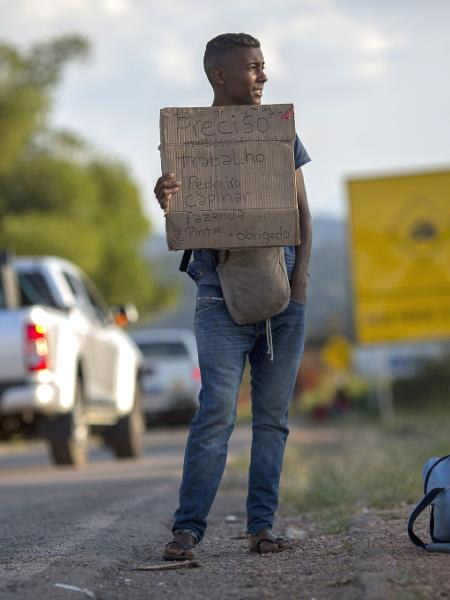 Refugiado venezuelano pede emprego em uma estrada perto de Pacaraima, no estado de Roraima - Mauro Pimentel/AFP