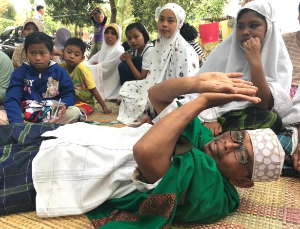 Narto Aryadi mostra como fez para cavar e escapar de escombros de mesquita após terremoto, em Lading-Lading, na Indonésia