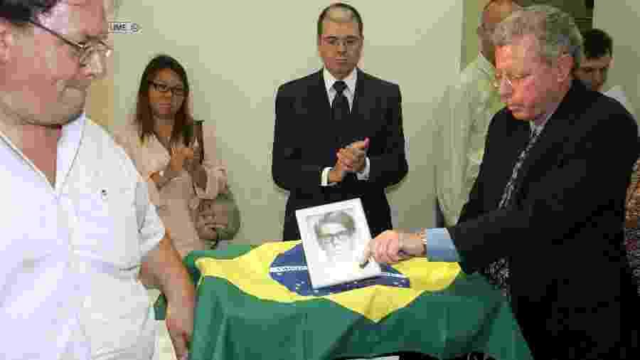 Gilberto Molina (à dir.) participa de cerimônia ao lado dos restos mortais do irmão Flavio - Ayrton Vignola/Folha Imagem - 10.out.2005