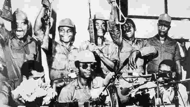 Em foto de 1980, o presidente da Libéria, Samuel K. Doe (óculos escuros), aparece cercado por membros de seu Conselho de Redenção dos Povos - Getty Image - Getty Image