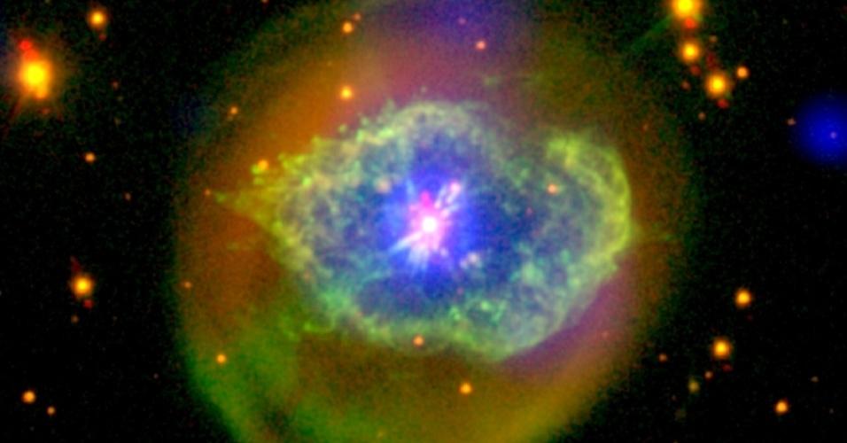 27.jul.2015 - Sob as cores vivas desta nuvem em forma de olho, chamada Abell 78, uma estrela morta, não muito diferente do nosso Sol, perde suas camadas exteriores para viver novamente. Liberar as camadas externas é o destino habitual para qualquer estrela com uma massa de 0,8 a 8 vezes a do Sol. Depois de esgotar o combustível de seus núcleos durante bilhões de anos, estas estrelas podem entrar em colapso e se tornar anãs brancas. Ao redor delas, o material ejetado atinge o gás ambiente e a poeira, criando nuvens conhecidas como 'nebulosas planetárias'. No entanto, o ressurgimento de vida visto nesta imagem é um evento excepcional. Apenas poucas estrelas que renasceram foram descobertas. Apesar de ter cessado a queima de gases nucleares, algumas das camadas exteriores da estrela se tornaram tão densas que a fusão do hélio recomeçou. A atividade nuclear renovada desencadeou outra, e a interação entre velhos e novos fluxos moldou a estrutura complexa da nuvem. A interação entre ventos lentos e rajadas rápidas no ambiente da Abell 78 aqueceram os gases a mais de um milhão de graus, tornando-a brilhante em visões de raio-X