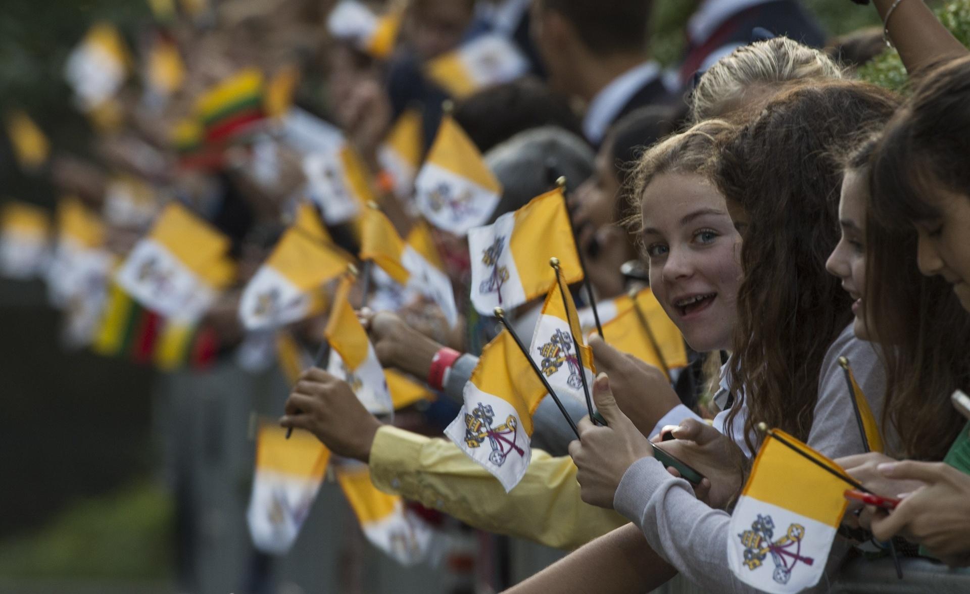 23.set.2015 - Crianças esperam pela chegada do papa Francisco na região do National Mall, em Washington, nos Estados Unidos, balançando bandeirinhas com o símbolo do Vaticano