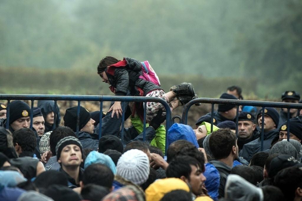 19.out.2015 - Um policial croata segura uma criança que atravessou uma grade de proteção, enquanto os imigrantes esperam na fronteira com a Sérvia. Cerca de três mil refugiados passaram a noite sob a chuva e o frio em solo sérvio junto à fronteira croata, por causa da aglomeração causada pelo fechamento da fronteira da Hungria com a Croácia