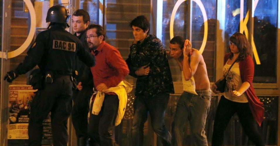 13.nov.2015 - Policiais evacuam pessoas próximas à sala de concertos Bataclan, em Paris, na França, onde um homem armado fez reféns. Agências de notícias falam em 100 pessoas dentro do local. Tiroteios e explosões aconteceram na noite desta sexta-feira (13) na capital francesa. A polícia relatou ao menos duas explosões nas proximidades do estádio Stade de France, onde o presidente francês, François Hollande, acompanhava um amistoso da seleção francesa