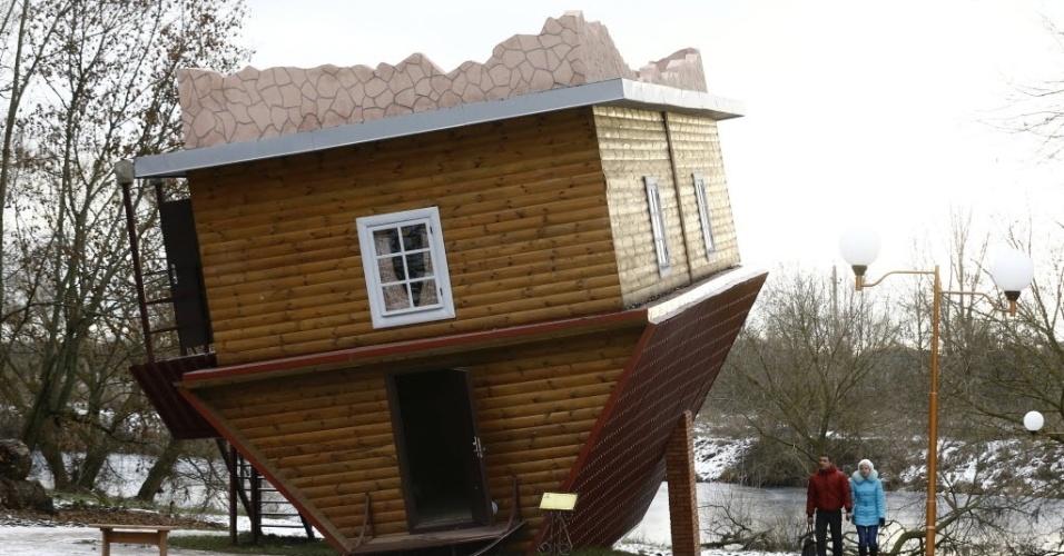 2.dez.2015 - Casal visita uma casa de cabeça para baixo em um complexo turístico perto da aldeia de Dukora, em Belarus. Dentro da casa todos os objetos são criados de cabeça para baixo, a fim de criar uma perspectiva especial para os visitantes