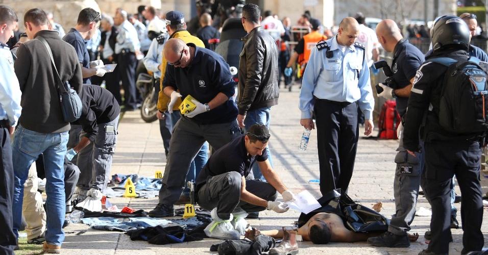 24.dez.2015 - Policiais forenses israelenses trabalham ao lado do corpo de palestino que, segundo as autoridades, foi morto a tiros pela polícia depois de realizar ataques contra civis ao lado de outro palestino perto do portão de Jaffa, na Cidade Velha de Jerusalém