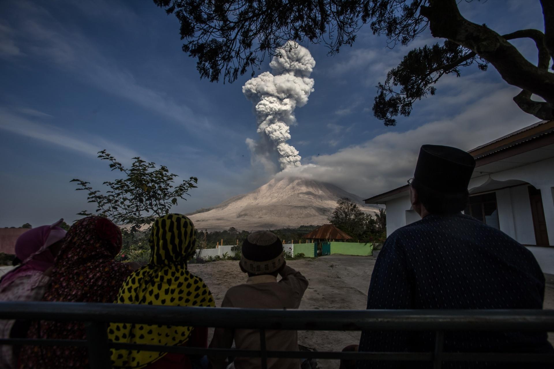 24.fev.2016 - Moradores da ilha de Sumatra, na Indonésia, assistem à erupção do Monte Sinabung. Autoridades locais vêm pedindo aos residentes paciência para enfrentar os impactos causados pela atividade do vulcão, que está prevista para continuar pelos próximos cinco anos