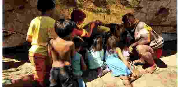 Um índio Waurá ensinando a mitologia em torno do guerreiro Kamukuwaká a crianças da aldeia usando as gravuras da caverna no Xingu antes do local ser vandalizado - Divulgação/People's Palace Project