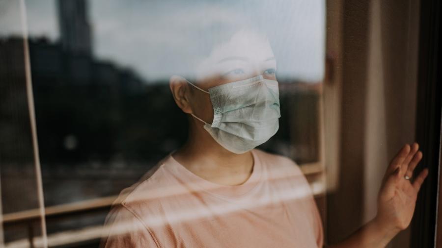 Mulher olhando pela janela durante isolamento social causado pela pandemia do novo coronavírus - Getty Images