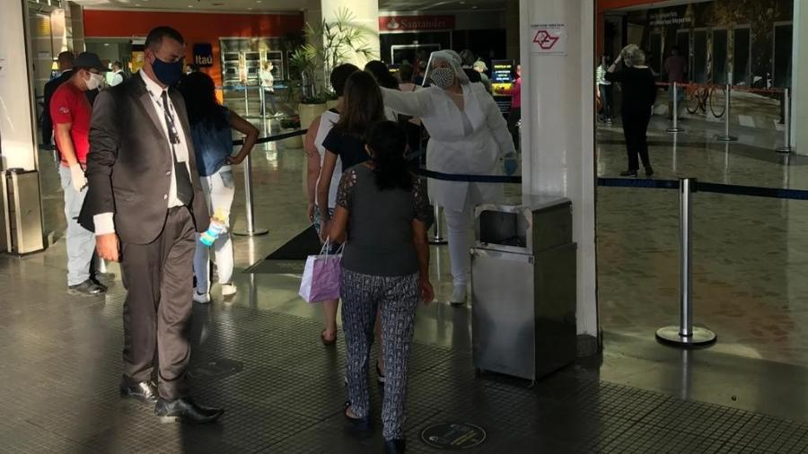 Funcionária mede a temperatura de frequentadores na entrada do Shopping Interlagos, em São Paulo  - Felipe Pereira/UOL