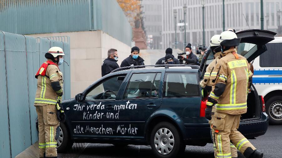 Bombeiros são vistos perto do carro que bateu no portão da entrada principal do escritório da chanceler alemã Angela Merkel, em Berlim - Fabrizio Bensch/Reuters
