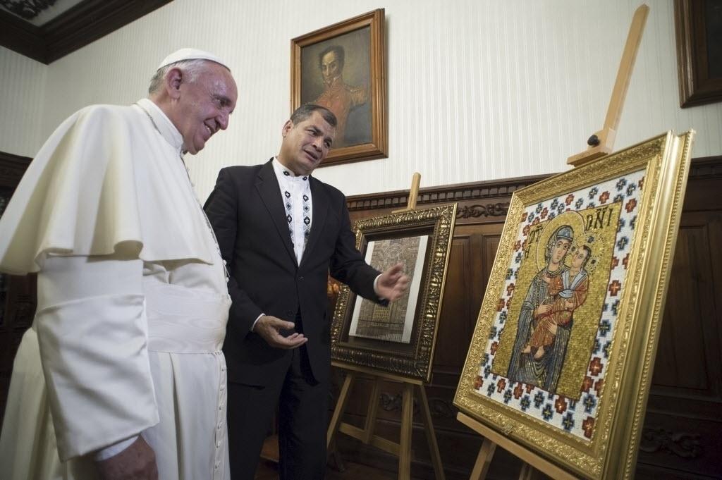 6.jul.2015 - O presidente do Equador, Rafael Correa, mostra alguns presentes ao papa Francisco no palácio presidencial em Quito