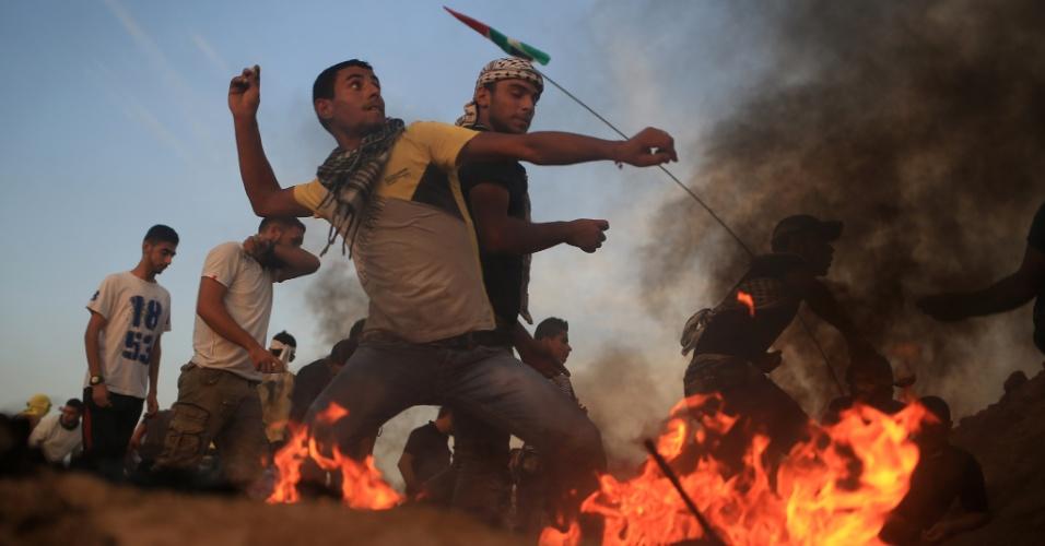 14.out.2015 - Manifestantes palestinos atiram pedras em soldados israelenses após derrubarem cerca na fronteira entre Israel e Bureij, no centro da faixa de Gaza. O surto de violência entre palestinos, as forças israelenses e colonos judeus nas últimas semanas aumentam os temores de uma terceira intifada, ou levante palestino