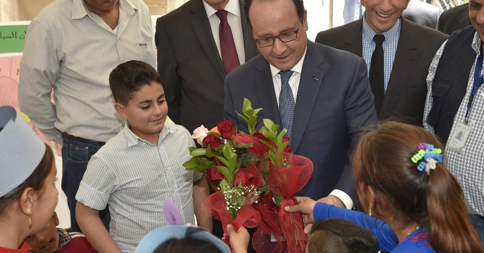 17.abr.2016 - Presidente da França, François Hollande, recebe flores de crianças refugiadas da Síria durante visita ao acampamento de Bekaa, Líbano