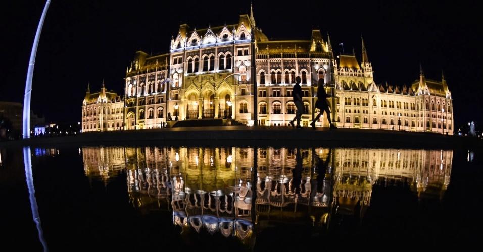 30.set.2016 - Casal caminha junto ao edifício do parlamento húngaro, em Budapeste, na Hungria