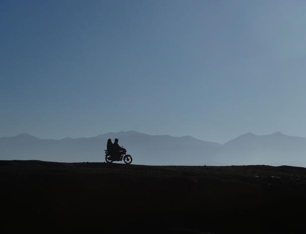 Casal anda de moto ao longo de estrada em Bamiyan, no Afeganistão