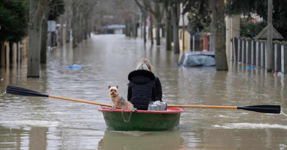 24.jan.2018 - Residente leva seu cachorro em um bote durante inundação das ruas da comuna de Villeneuve-Saint-Georges, na França