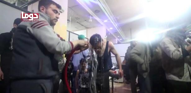 Voluntários limpam corpo de homem após suposto ataque químico em Douma, perto de Damasco