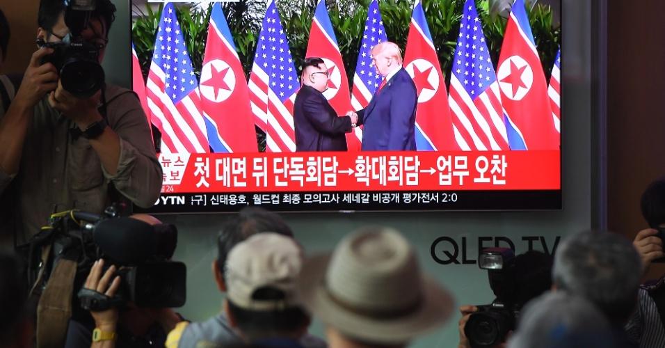 11.jun.2018 - Por uma televisão na estação de trem em Seul, sul-coreanos acompanham o aperto de mão histórico entre Donald Trump e Kim Jong-un