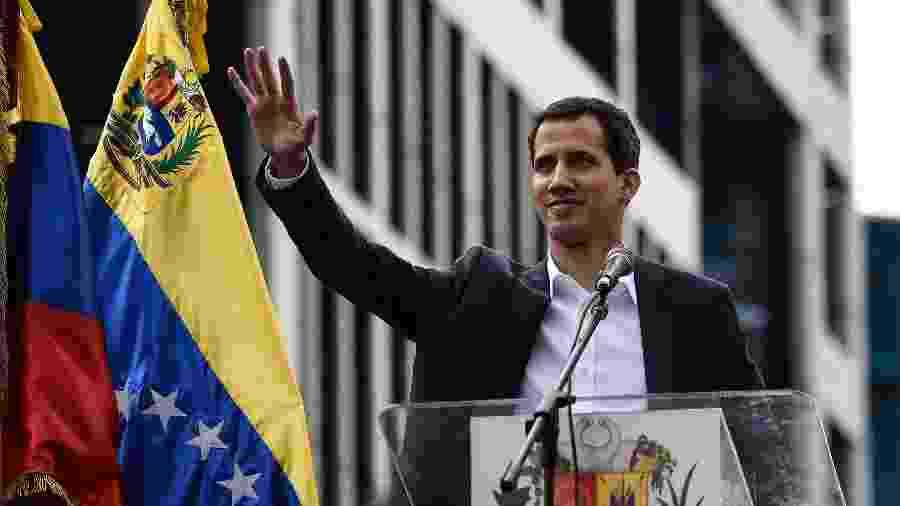 """23.jan.2019 - O chefe da Assembléia Nacional da Venezuela, Juan Guaido, acena para a multidão durante uma manifestação de massas contra o líder Nicolas Maduro, em que ele se declarou o """"presidente interino"""" do país em 23 de janeiro de 2019, em Caracas - Federico PARRA / AFP"""