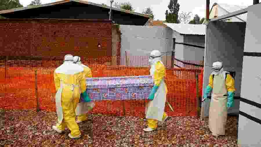 Profissionais de saúde usam equipamentos de proteção individual enquanto carregam o caixão de uma mulher congolesa morta por ebola - Baz Ratner/Reuters