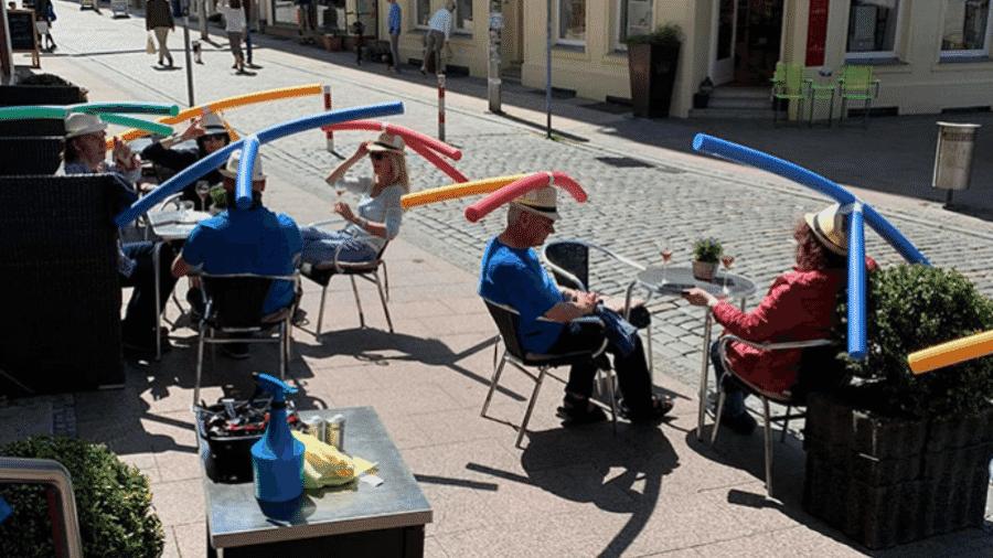 Clientes usam chapéu com macarrão de piscina para manter a distância social, em um café na cidade alemã de Schwerin - Reprodução