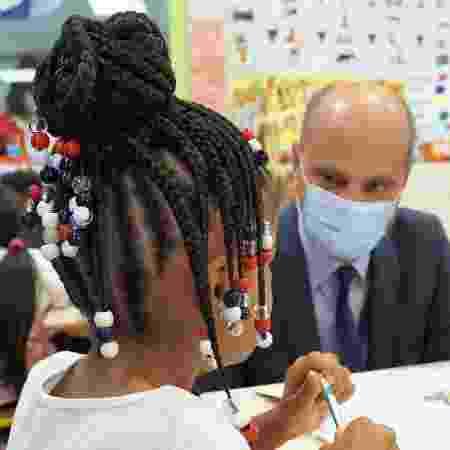 1.set.2020 - O ministro da Educação e Esporte da França, Jean-Michel Blanquer, conversa com uma criança no primeiro dia de volta às aulas no país após a paralisação por causa da pandemia do coronavírus - Guillaume Souvant/AFP